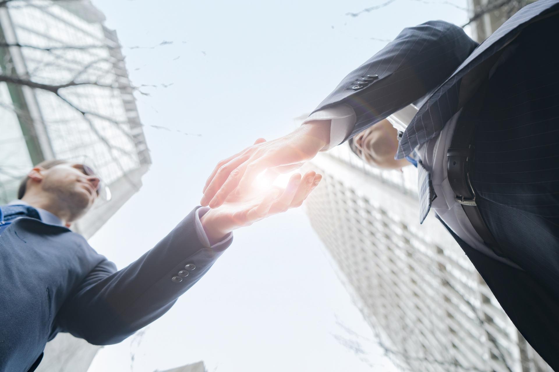 都会で握手をするビジネスマン
